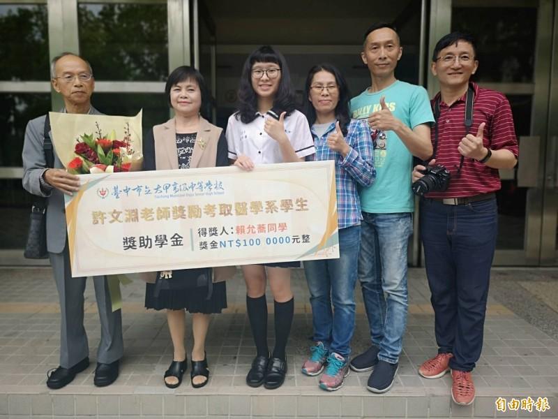 許文淵老師伉儷(左起),頒發百萬獎學金給賴允蕎(中)。(記者張軒哲攝)