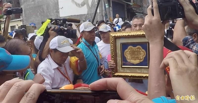 謝惠仁第一個走向鑾轎,向媽祖獻上金牌。(記者陳冠備攝)