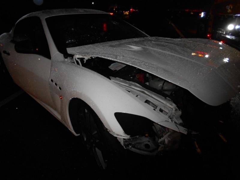 名貴轎車瑪莎拉蒂在國道上奔馳時,因打滑失控自撞護欄,車頭全毀。(記者鄭名翔翻攝)(記者鄭名翔攝)