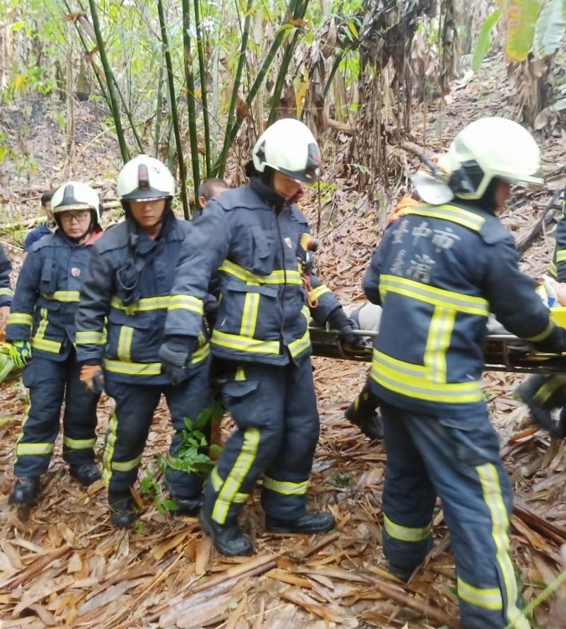 一名方姓男子,今天中午開車在霧峰桐林山區衝下邊坡受困車內,20多名消防人員將他救出後抬到路面。(記者陳建志翻攝)