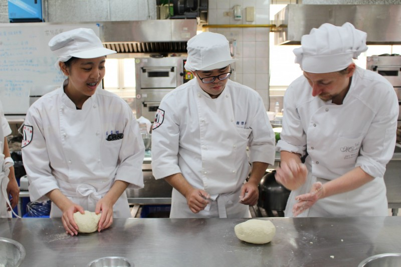 德師Jan Mächler與學生示範德式麵包製作,純熟的技法更讓學生讚嘆。(南臺科大提供)
