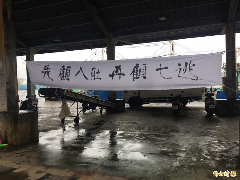 漁民在正濱漁港懸掛「先顧八肚 再顧七逃」等布條反對開放漁港垂釣。(記者林欣漢攝)