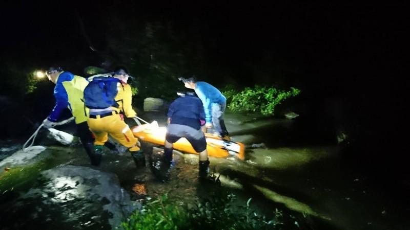 警消人員冒險涉過多段溪流,將周姓男子遺體運下山。(記者佟振國翻攝)
