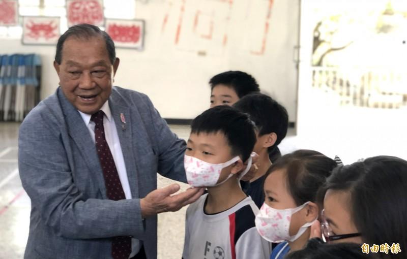 康那香企業董事長戴榮吉(左一)為學童戴上防PM2.5的3D立體口罩。(記者楊金城攝)