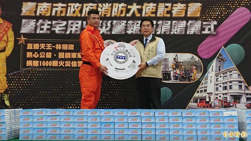 直播主林揚竣(左)捐一千個住宅用火災警報器給南市消防局,市長黃偉哲代表接受。(記者王俊忠攝)