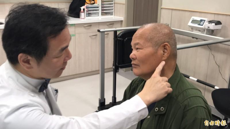 中國醫藥大學新竹附設醫院心臟血管科主任林圀宏(左)手指著葉姓老翁的左耳耳垂下緣,讓大家看清楚所謂的耳垂摺痕。(記者黃美珠攝)