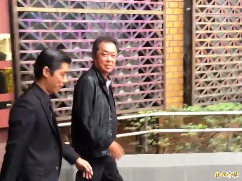 知名導演朱延平(右)遭台北地檢署傳喚出庭,訊後面對記者追問,僅微笑未受訪。(記者錢利忠攝)