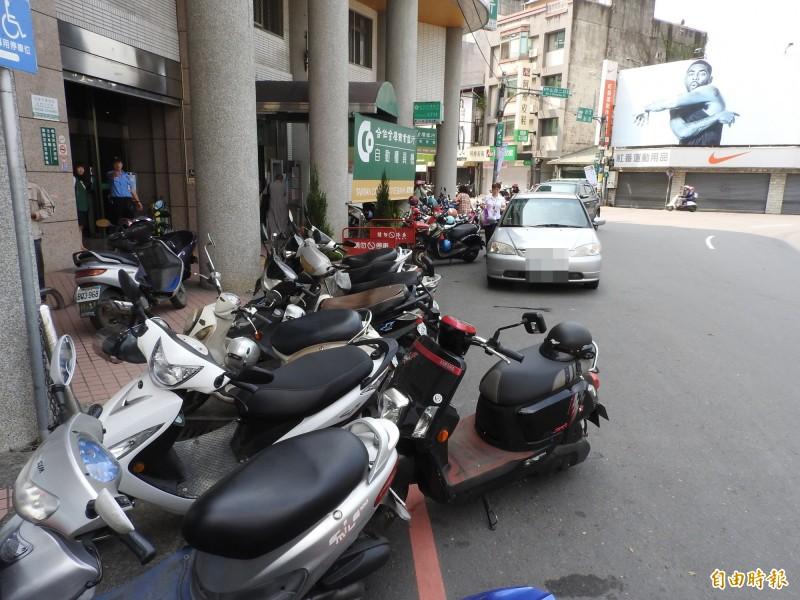 埔里中正路合作金庫圓環旁劃設紅線區也停滿汽、機車。(記者佟振國攝)