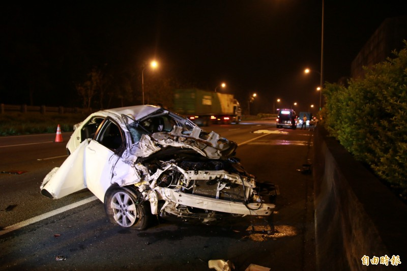 白色自小客車撞上護欄,車身全毀,車殼零件四散。(記者鄭名翔攝)
