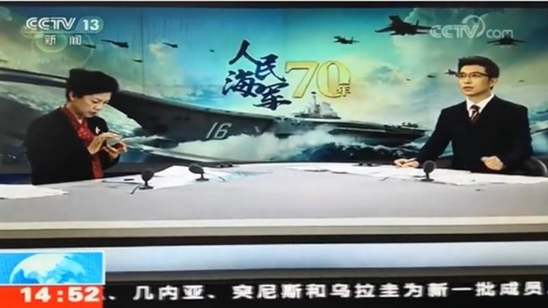 中國央視在直播青島海軍檢閱儀式時,低頭滑手機的畫面不慎播了出去。(網路影片截圖)