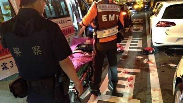 警、消人員救護遭人圍毆重創的陳姓男子,路面上血跡斑斑。(記者王俊忠攝)