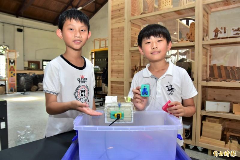 學進國小學生簡雋(右)、蔣秉晏(左)設計的防水插座組,可在淹水到達一定高度時,彈出插頭讓插座密封避免進水,這項裝置近期獲得世界青少年發明展台灣選拔賽金牌,將代表台灣赴印尼參賽。(記者張議晨攝)
