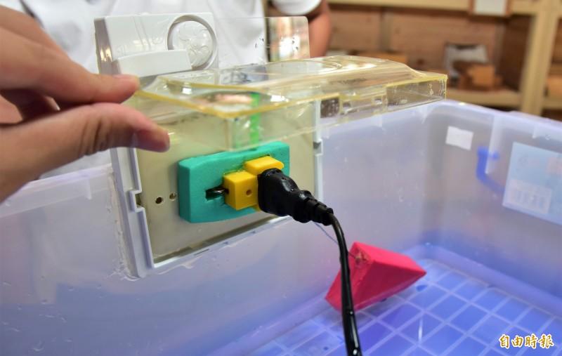 學進國小學生簡雋、蔣秉晏設計的防水插座組,可在淹水到達一定高度時,彈出插頭讓插座密封避免進水。(記者張議晨攝)