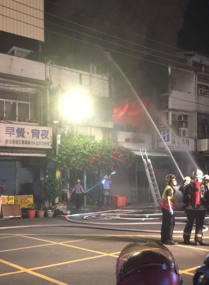 台中大里好來一街一棟民宅今晚8點多起火燃燒,消防人員獲報緊急出水灌救,未讓火勢延燒。(記者陳建志翻攝)