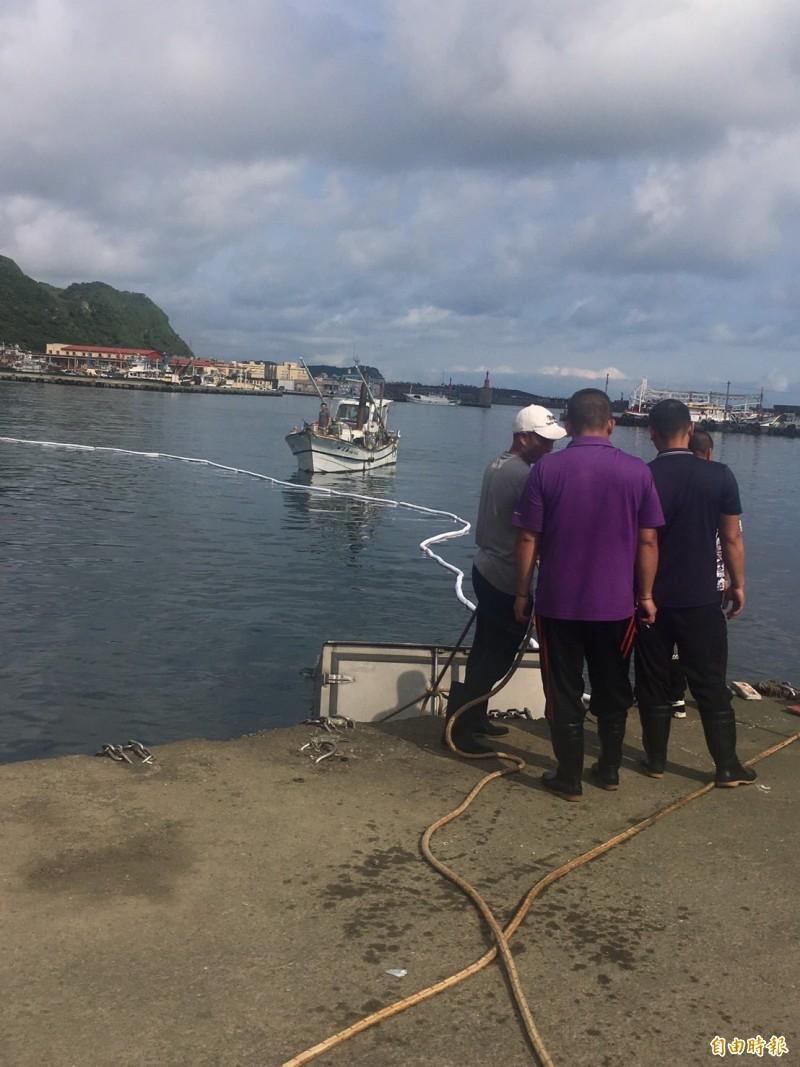 北區製冰廠羅姓老闆將3輛3.5噸貨車開入海中,留在現場處理貨車打撈,海巡擔心油汙汙染漁港,佈放攔油索,在旁警戒。(記者林嘉東攝)