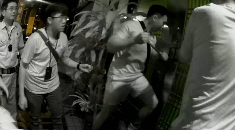 員警使用鐵鍬踹門攻破賭場大門。(記者黃佳琳翻攝)