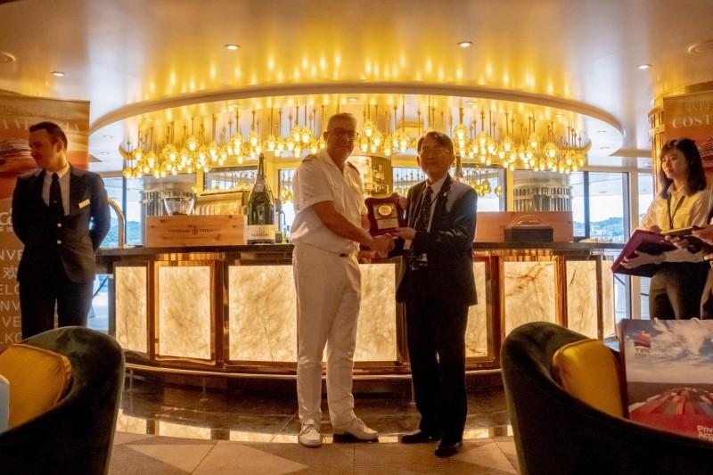 歌詩達郵輪威尼斯號基隆港首航,基隆港務分公司總經理劉詩宗(右)致贈首航紀念牌給船長。(基隆港務分公司提供)