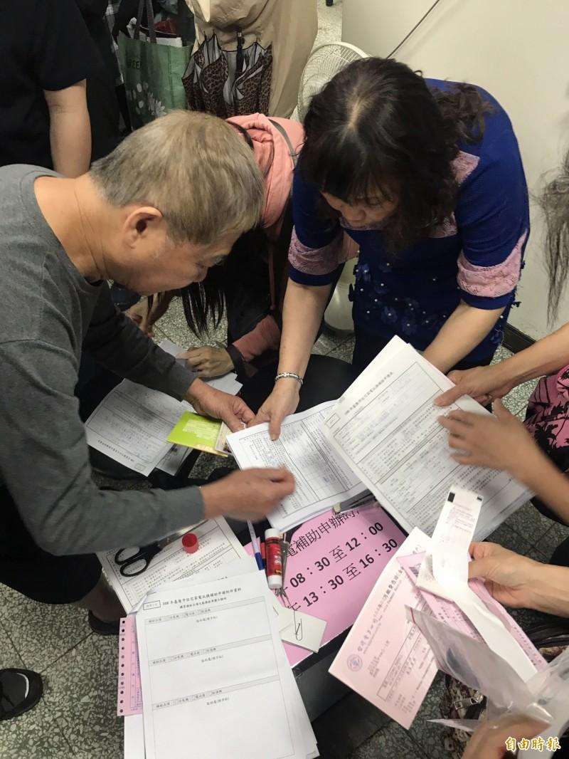 民眾在現場填寫節電補助相關文件資料。(記者林欣漢攝)