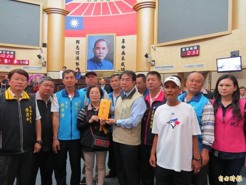 沿海養殖漁民反種光電,赴市議會抗議陳情,由正在備詢的台南市長黃偉哲收入陳情書。(記者蔡文居攝)