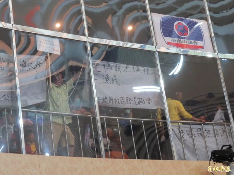 漁民在南市議會旁聽席拉布條抗議,反對種光電。(記者蔡文居攝)