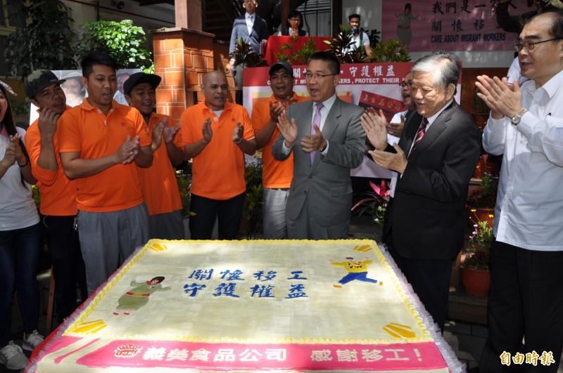 內政部長徐國勇(中)與移工們開心唱歌、切蛋糕。(記者周敏鴻攝)