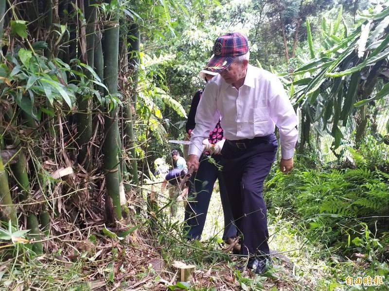 關西鎮住在飛鳳古道旁的94歲徐雲銓也加入志工行列,老當益壯,和年輕人一樣拿著鐮刀砍除遮擋路徑的竹子。(記者廖雪茹攝)