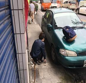 年輕車手在路邊車輛旁拿取詐騙現金。(翻攝畫面)