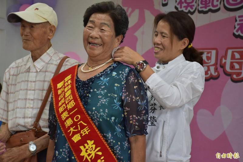 台西鄉長林芬瑩(後)為模範母親林丁梅花(前)戴上項鍊。(記者林國賢攝)