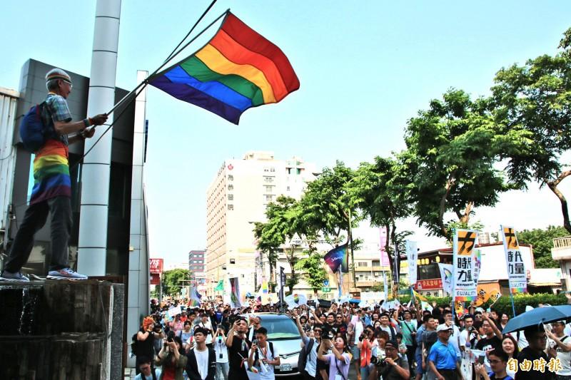 苗栗縣性別平權遊行今天舉行,同運平權運動、同婚釋憲申請人祁家威(左)站高處揮舞彩虹旗,隊伍群眾大聲歡呼打氣。(記者鄭名翔攝)