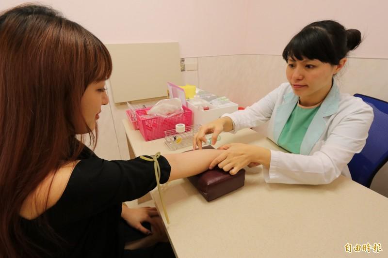 亞大醫院加護病房護理長蔣玉珍(右)表示,民眾抽血後要避免瘀青,除不可搓揉傷口,須以棉花加壓止血5分鐘。圖為情境照,圖中人物與本文無關。(記者陳建志攝)