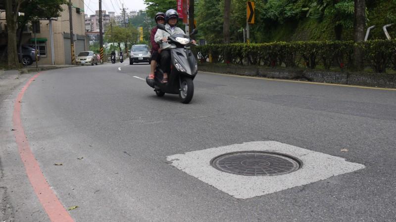 民眾反映,基隆市基金一路路段的人孔蓋,因天雨濕滑,常有機車騎士摔車,險象環生。(立委蔡適應服務處提供)