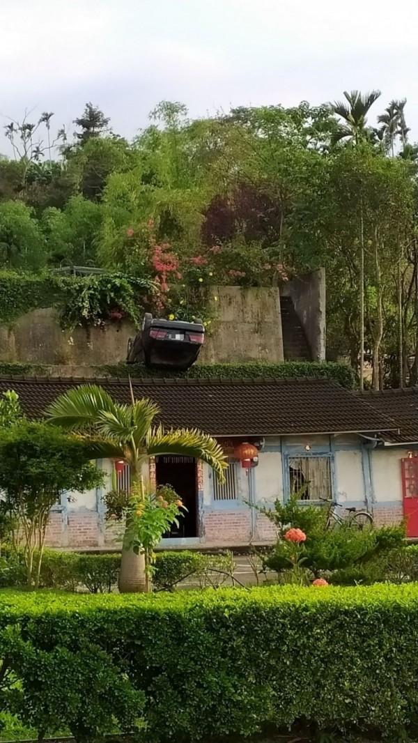 小客車倒車翻落,差點壓到民宅屋頂。(記者林宜樟翻攝)