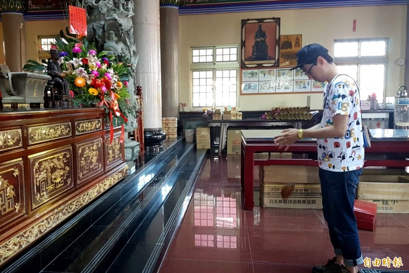 日本遊客三品政人參拜富安宮的義愛公,一連擲出4個聖筊。(記者林宜樟攝)