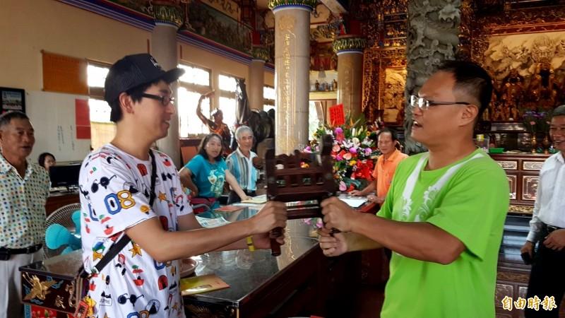 日本遊客三品政人參拜富安宮,了解觀手轎的方式。(記者林宜樟攝)