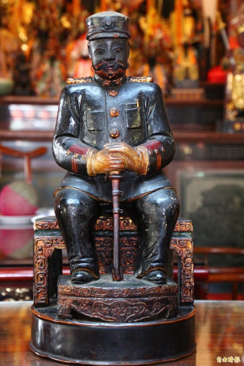 日本遊客三品政人參拜富安宮的義愛公。(記者林宜樟攝)