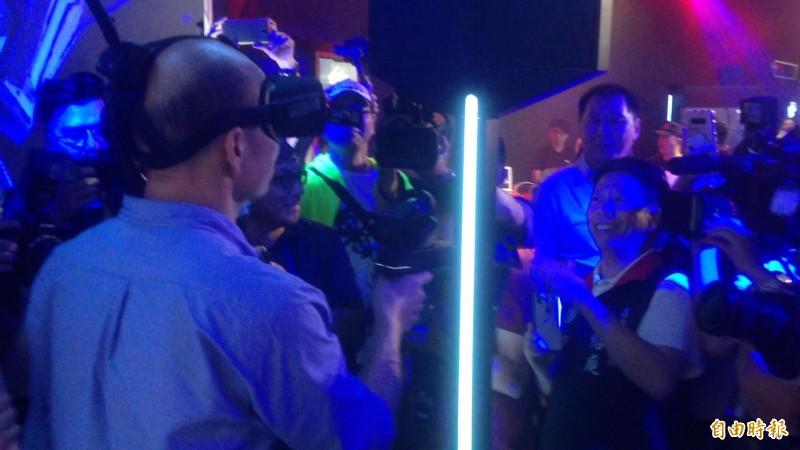高雄市長韓國瑜持VR槍射擊,高雄市議員黃紹庭(右)作勢閃躲玩樂。(記者黃旭磊攝)