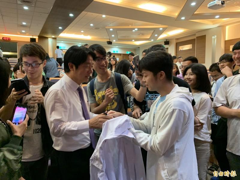 賴清德到中山附醫為學生演講,受到學生歡迎,簇擁合照、簽書,並在白袍上簽名。(記者蔡淑媛攝)