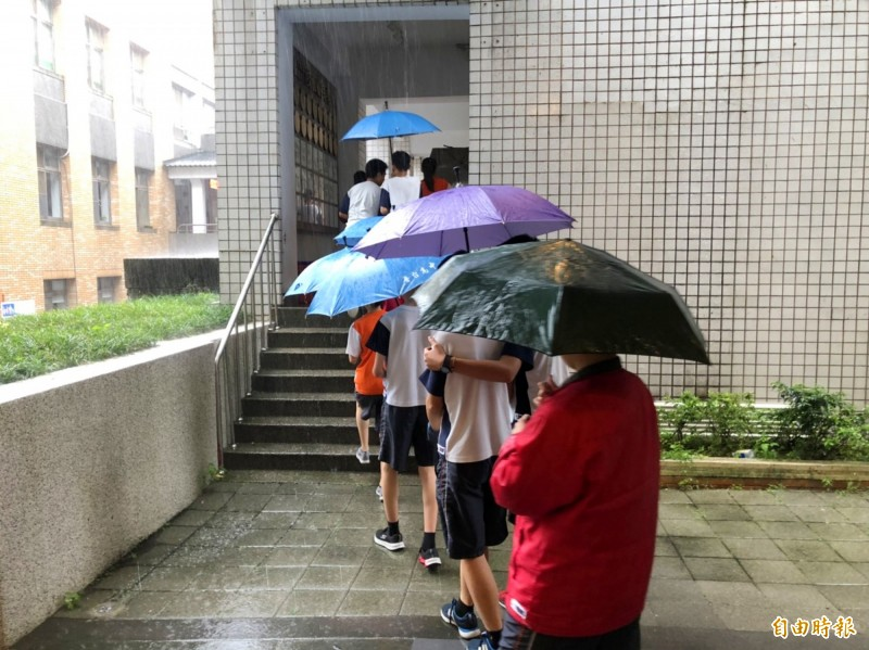 下午下起大雨,在暨大附中考試的會考考生,仍冒雨看試場。(記者陳鳳麗攝)