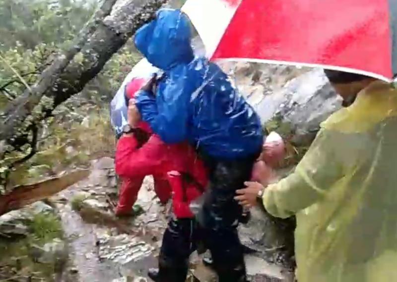 登山客在玉山疑因雷擊受傷,由揹工揹到登山步道口,消防員接駁送醫。(記者林宜樟翻攝)
