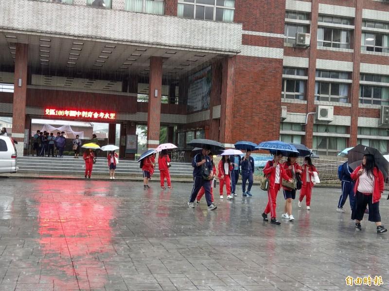 國中會考登場,南投考區一整天都在下雨,考生進出考場都得撐傘,相當不方便。(記者劉濱銓攝)
