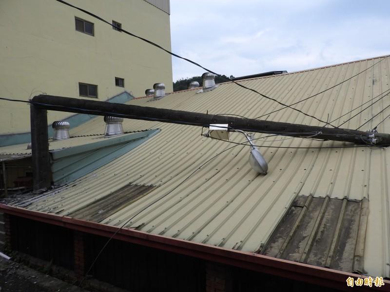 另一根電線桿折斷後橫躺在民宅屋頂。(記者佟振國攝)