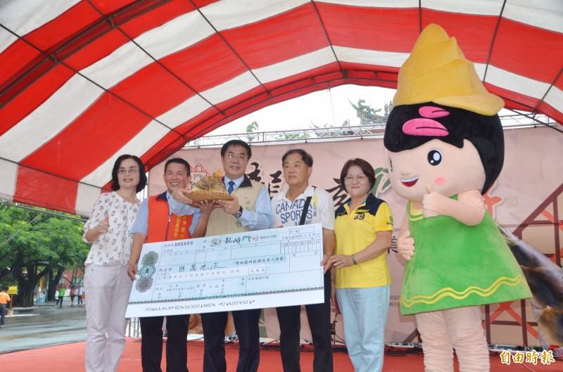 市長黃偉哲(中)協助冠軍筍義賣,出身當地的企業家黃松水(右2)以6萬元得標。(記者吳俊鋒攝)