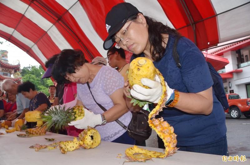 現場頗受矚目的削鳳梨趣味競賽,選手專注於刀工,力求佳績。(記者吳俊鋒攝)