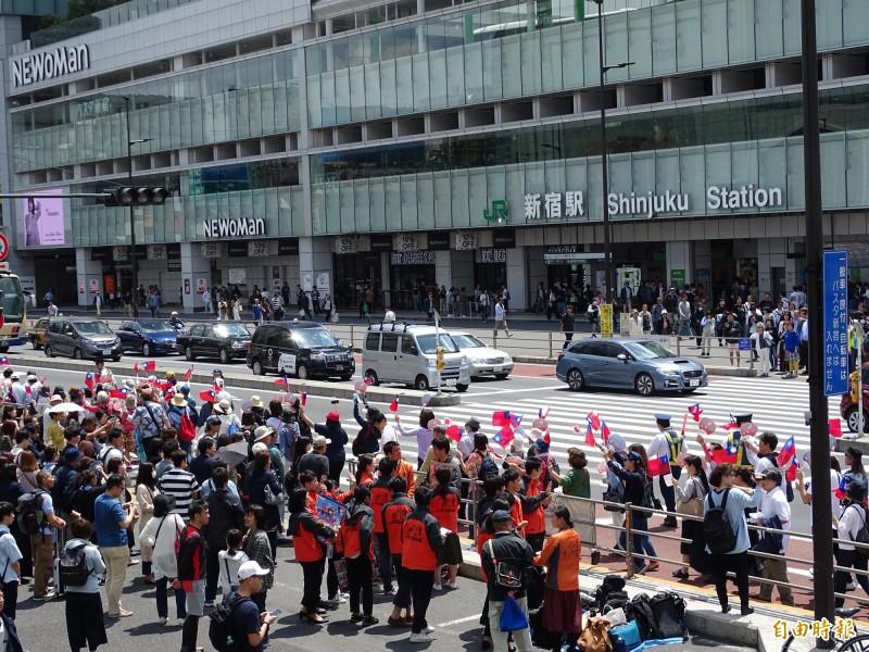 日本僑界舉辦挺台遊行,隊伍行經新宿車站南口引起群眾圍觀。(記者林翠儀攝)