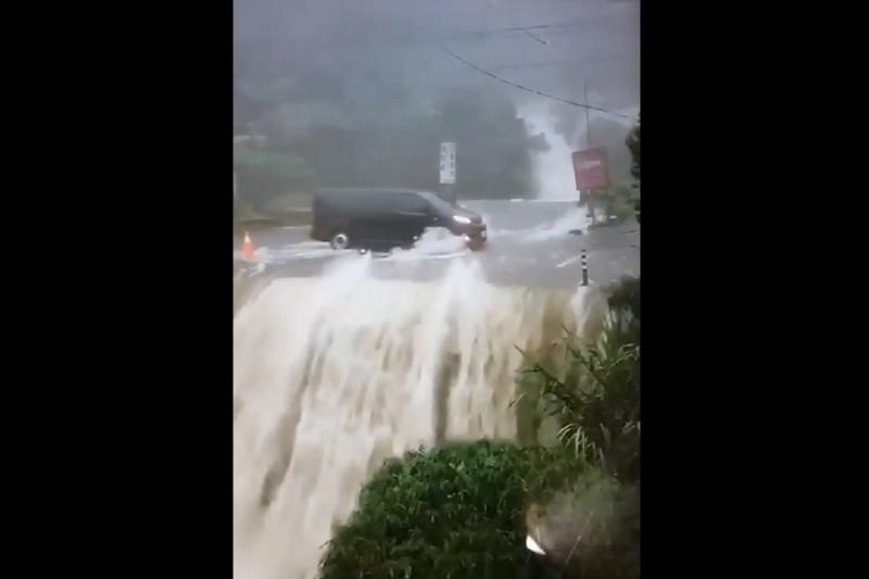 南投鹿谷野溪山洪爆發,大量溪水倒灌漫過路面有如瀑布,往來車輛冒險行經讓人捏把冷汗。(民眾提供)