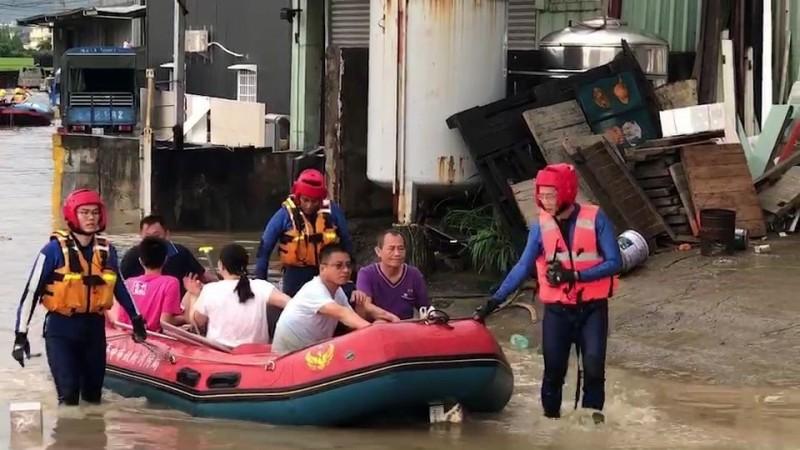 台中烏日環河路1段淹水近1人高,造成附近20多名工廠員工受困,消防人員出動橡皮艇將人救出。(記者陳建志翻攝)