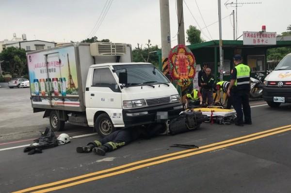 消防員鑽入車底,以頂舉袋及油壓器材將貨車撐起,救出受困騎士。(記者鄭名翔翻攝)