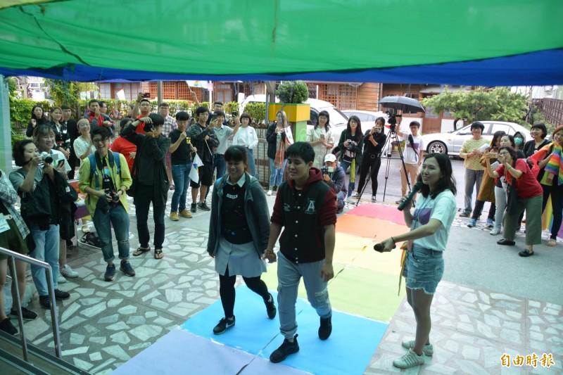 新人在親友簇擁下,踏上彩虹紙毯,並穿過彩虹布簾隧道後,走入花蓮戶政事務所完成登記。(記者王峻祺攝)