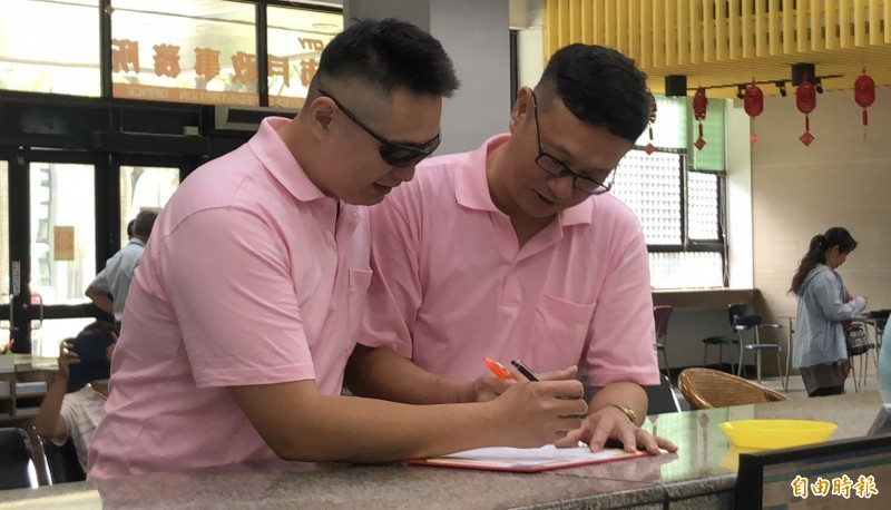 謝佳霖(右)和另一半林先生到屏東市戶政事務所登記同婚。(記者羅欣貞攝)