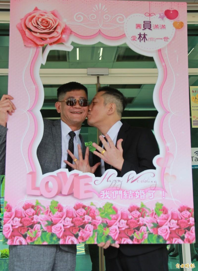 男性伴侶王富生(右)與沈其祥(左)辦理結婚登記,大方秀出媽媽贈送的金戒指。(記者陳冠備攝)